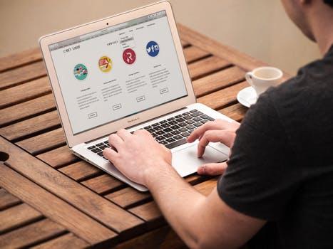 Man at desk using website on laptop